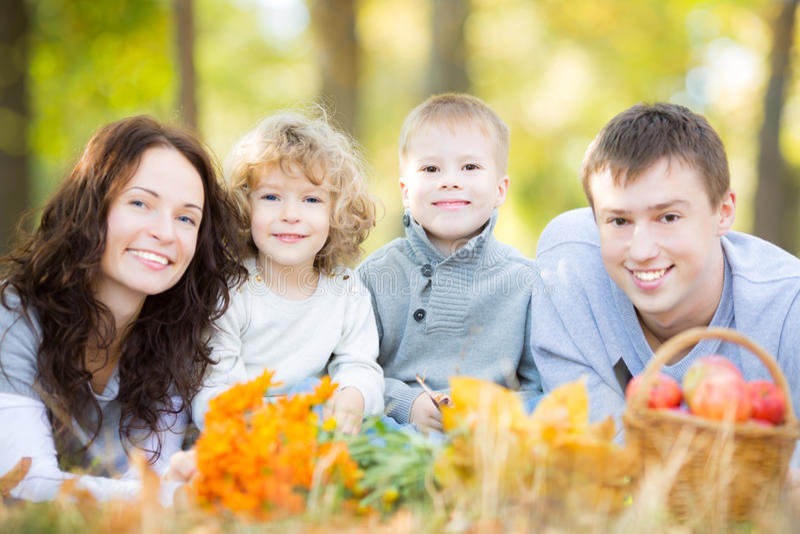 Familia feliz que tiene comida campestre en parque del otoño imagenes de archivo