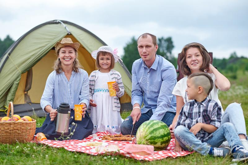 Familia feliz que tiene comida campestre en prado en un día soleado Familia que disfruta de acampada en campo fotos de archivo libres de regalías