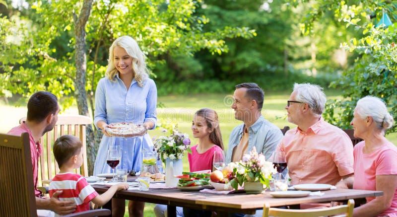 Familia feliz que tiene la cena o la fiesta de jardín del verano foto de archivo