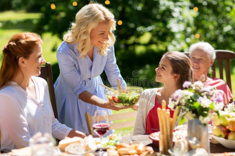Familia feliz que tiene la cena o la fiesta de jardín del verano imagenes de archivo