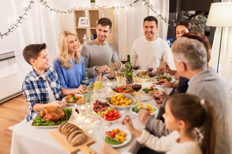 Familia feliz que tiene partido de cena en casa imagen de archivo