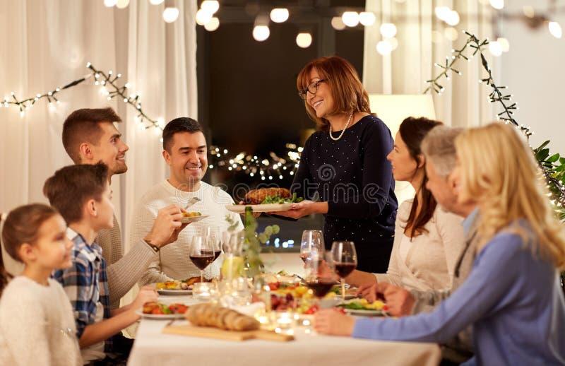 Familia feliz que tiene partido de cena en casa imagen de archivo libre de regalías