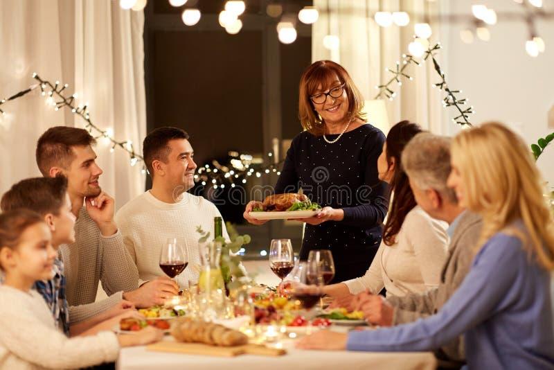 Familia feliz que tiene partido de cena en casa foto de archivo libre de regalías