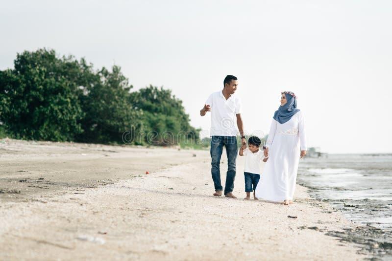 Familia feliz que tiene tiempo de la diversión que camina junto en la playa situada en Pantai Remis imágenes de archivo libres de regalías