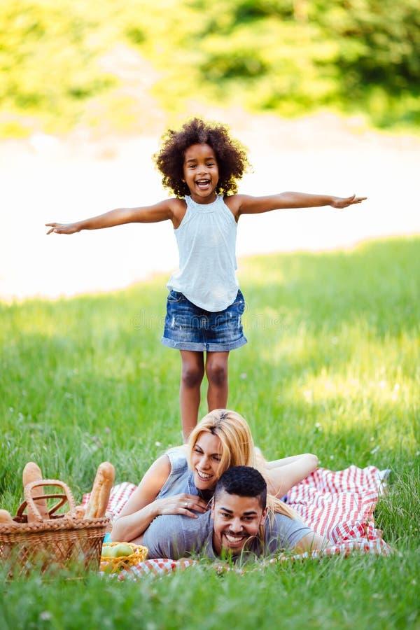 Familia feliz que tiene tiempo de la diversión en comida campestre fotografía de archivo libre de regalías