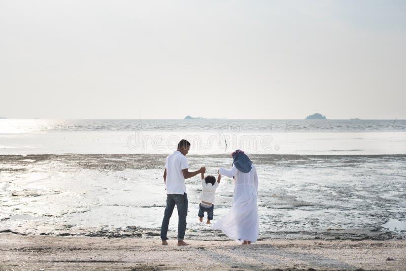 Familia feliz que tiene tiempo de la diversión junto en la playa situada en Pantai Remis imagen de archivo libre de regalías