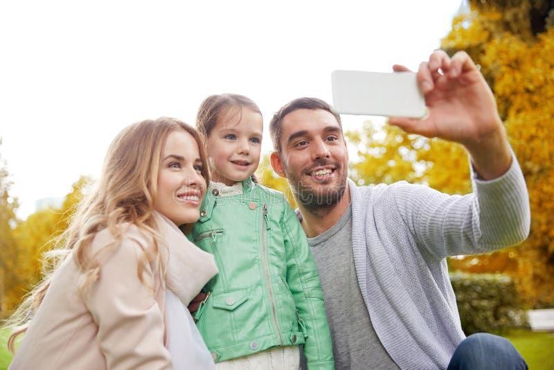 Familia feliz que toma el selfie por smartphone al aire libre fotografía de archivo libre de regalías