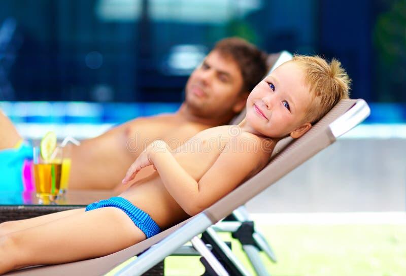 Familia feliz que toma el sol cerca de la piscina imagen de archivo