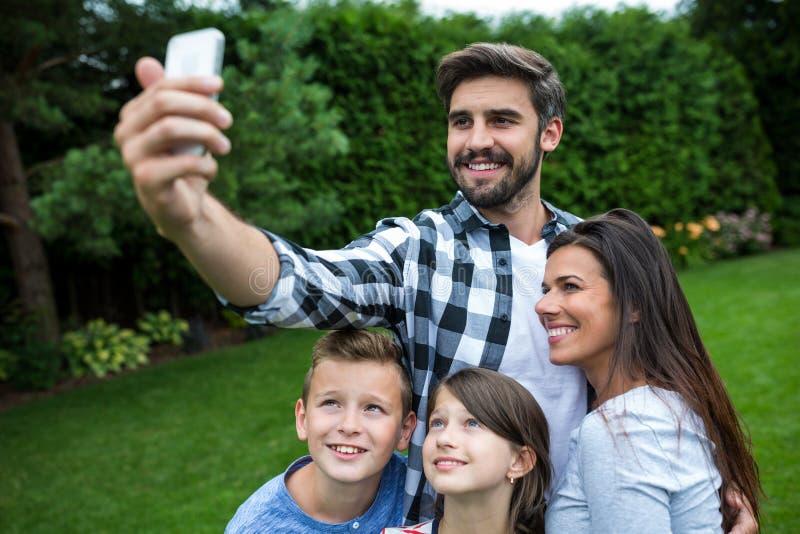 Familia feliz que toma un selfie del teléfono móvil en parque imagenes de archivo