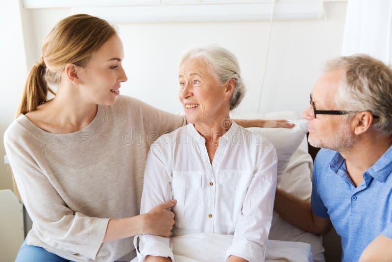 Familia feliz que visita a la mujer mayor en el hospital fotos de archivo libres de regalías