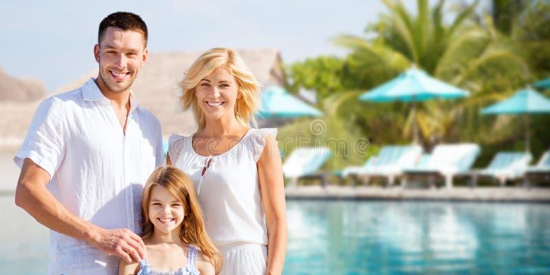 Familia feliz sobre piscina del centro turístico del hotel imagenes de archivo