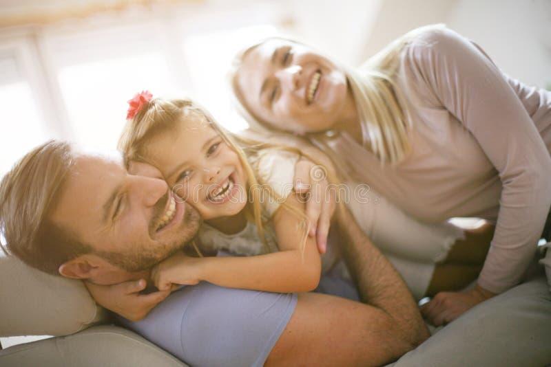 Familia feliz sonriente en casa junto imagenes de archivo