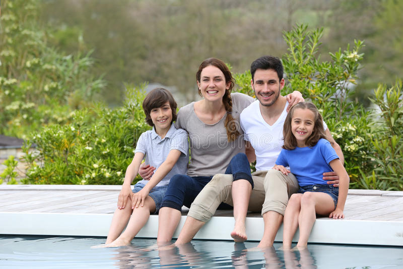 Familia feliz sonriente por la piscina foto de archivo