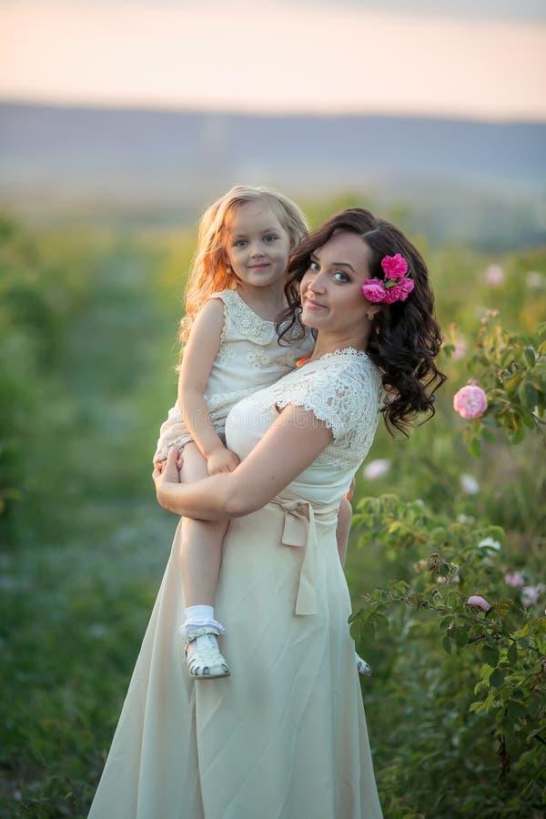 Familia feliz: una mujer embarazada hermosa joven con su pequeña hija linda que camina en el campo anaranjado del trigo en a imagen de archivo