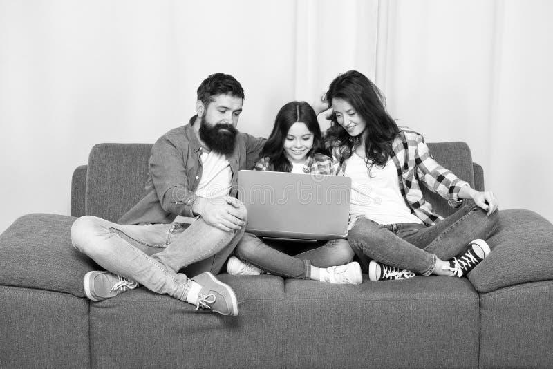 Familia feliz usando la computadora port?til estancia en l?nea Ni?a con los padres madre y padre barbudo con la hija que mira fotografía de archivo
