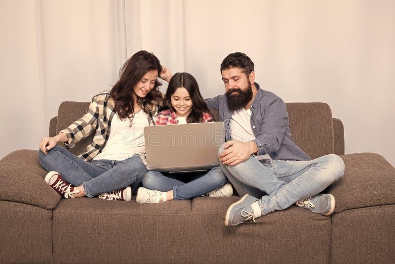 Familia feliz usando la computadora port?til estancia en l?nea Ni?a con los padres madre y padre barbudo con la hija que mira imagen de archivo libre de regalías