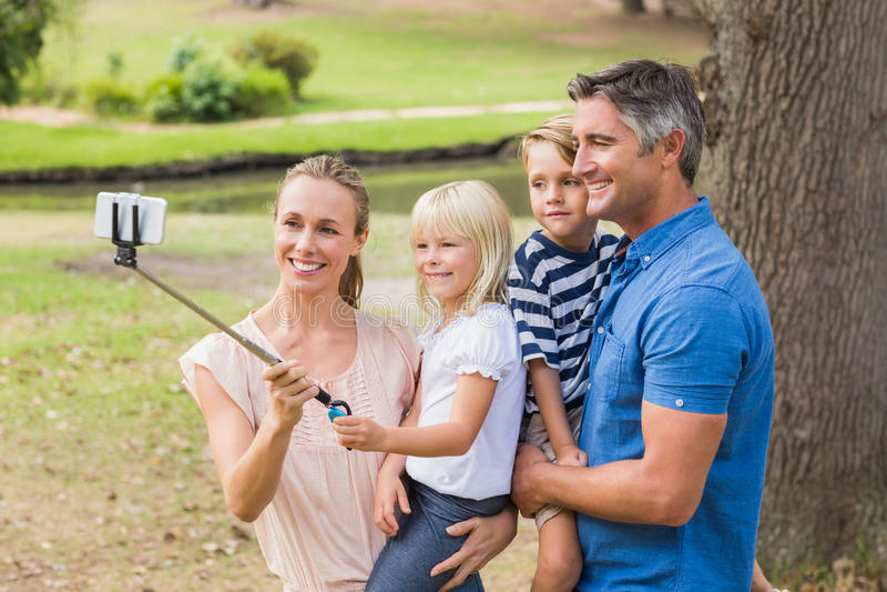 Familia feliz usando un palillo del selfie en el parque fotografía de archivo libre de regalías