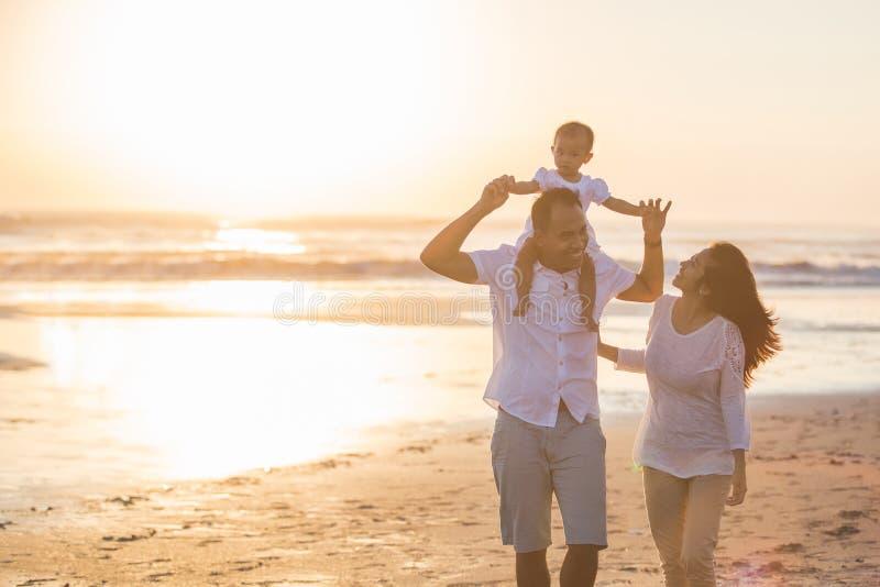 Familia feliz y bebé que disfrutan de puesta del sol en el ocio del verano fotografía de archivo libre de regalías