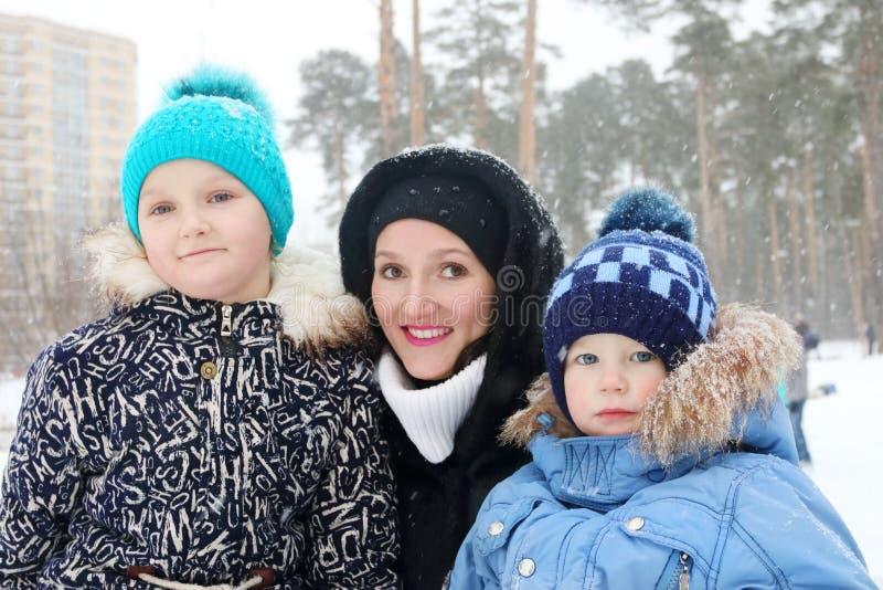 Familia feliz y x28; madre, hija, son& x29; actitud durante las nevadas imágenes de archivo libres de regalías