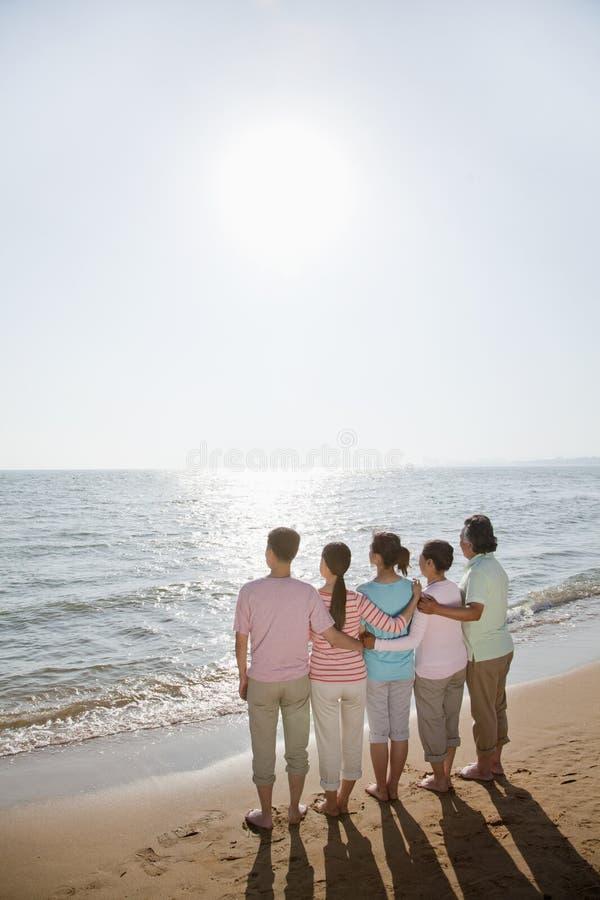 Familia generacional multi, brazos alrededor de uno a por la playa, vista posterior imagen de archivo