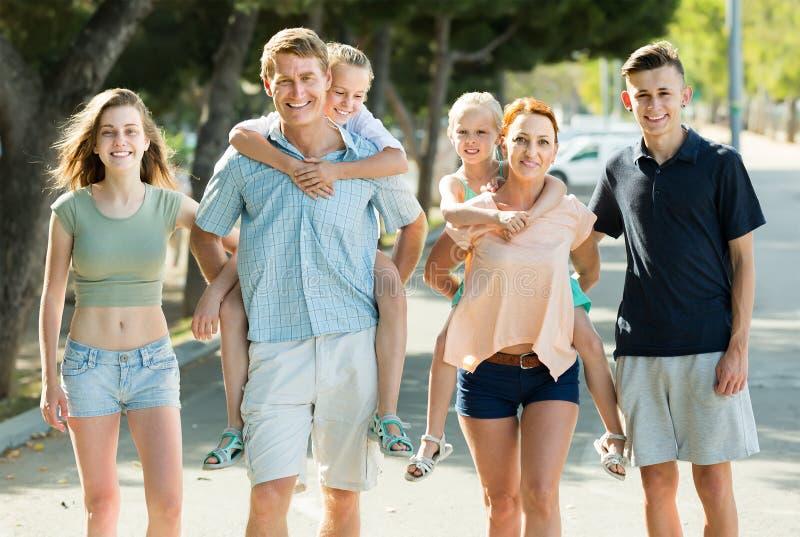 Familia grande de seis personas que caminan con los niños en padres detrás adentro imagenes de archivo