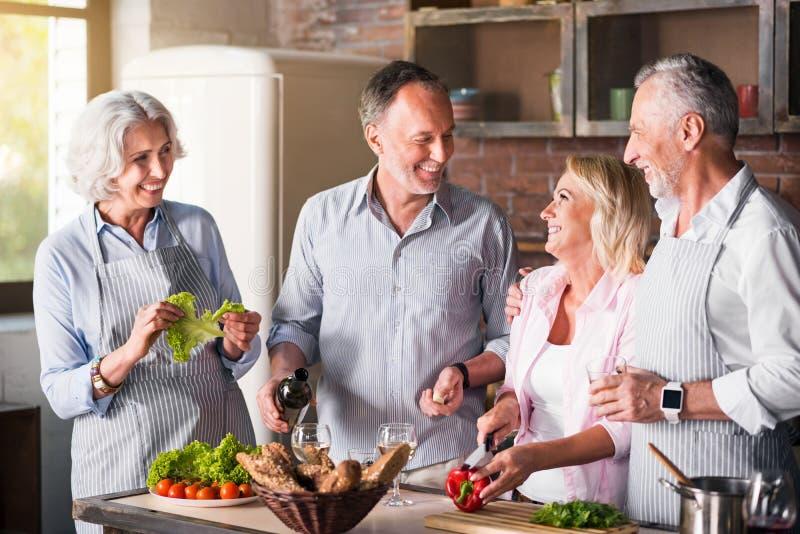 Familia grande que cocina en la cocina junto foto de archivo