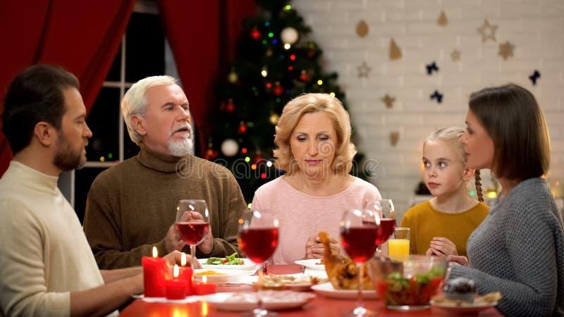 Familia grande que ruega antes de la cena tradicional de Navidad, decoraciones que chispean en árbol imagen de archivo libre de regalías