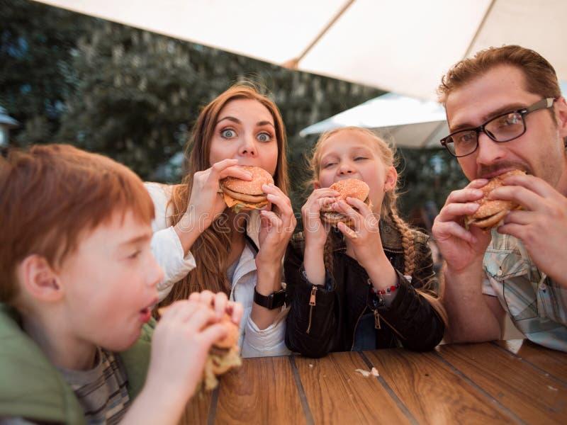 Familia hambrienta que come las hamburguesas, sentándose en una tabla en un restaurante de los alimentos de preparación rápida fotos de archivo