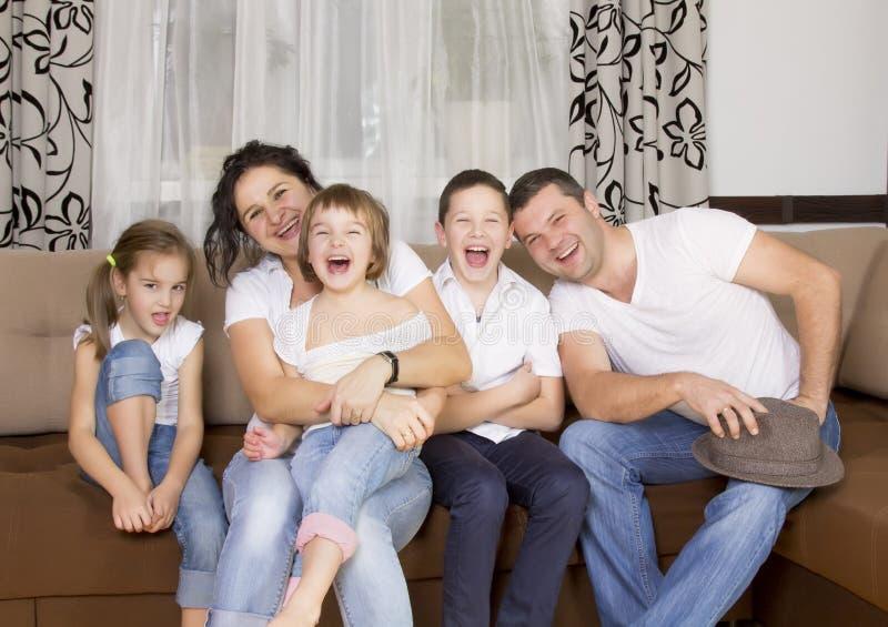 Familia hermosa alegre junto que se ríe a casa durante el h foto de archivo libre de regalías