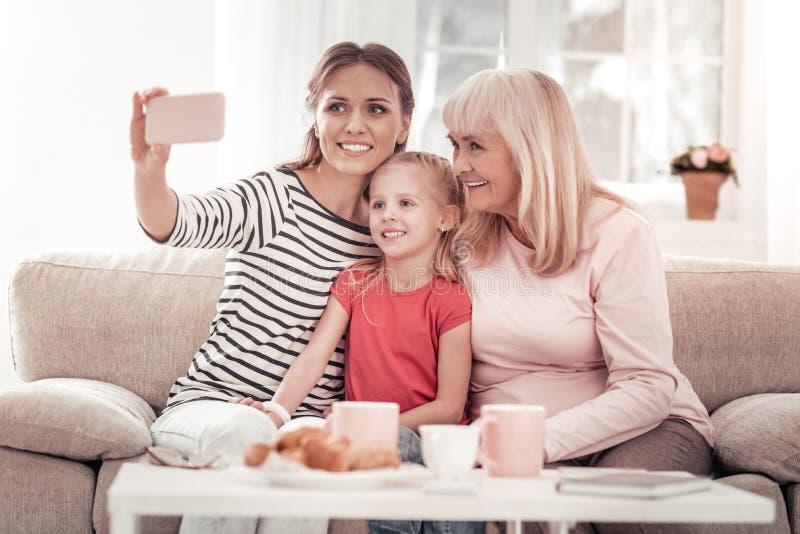 Familia hermosa de tres fotos de fabricación en un teléfono móvil foto de archivo