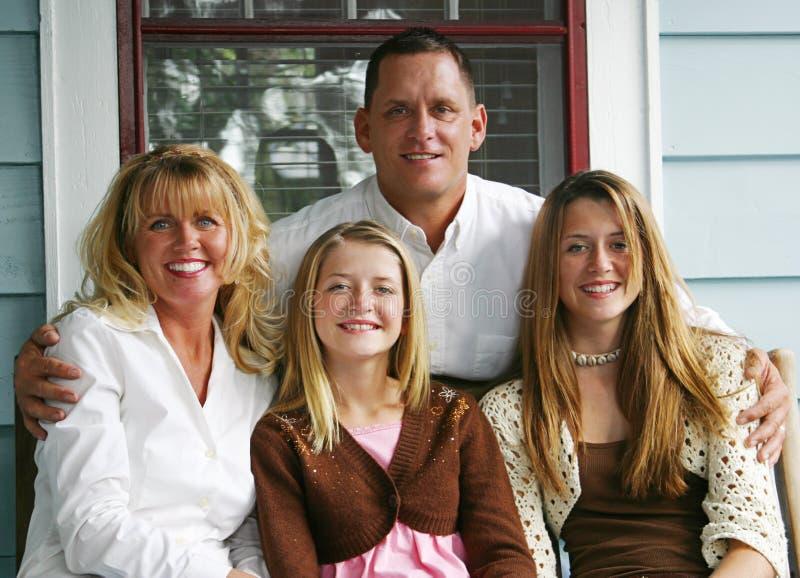 Familia hermosa en el pórche de entrada imágenes de archivo libres de regalías