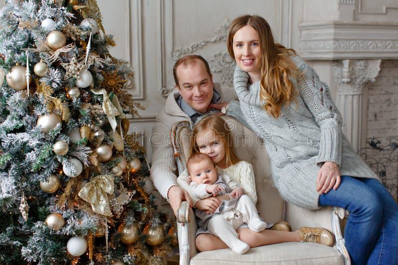 Familia hermosa en los suéteres hechos punto que se sientan en una silla en el b fotografía de archivo