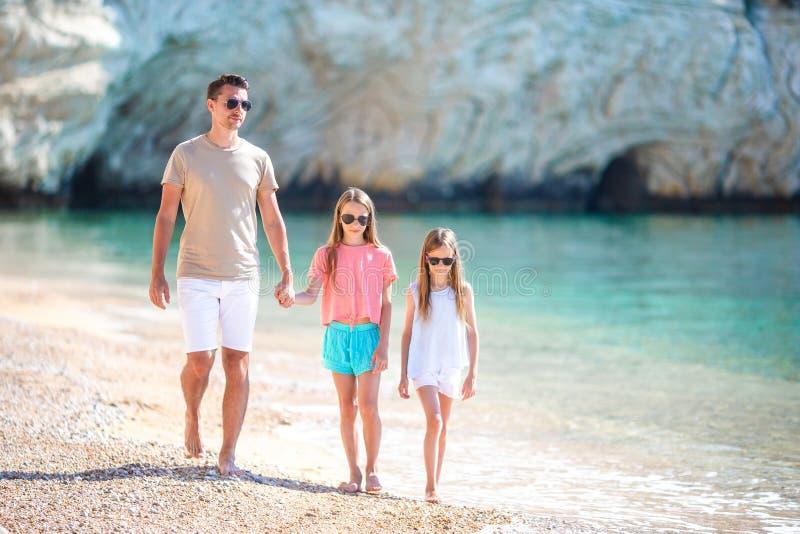 Familia hermosa feliz de papá y de niños en la playa blanca foto de archivo libre de regalías