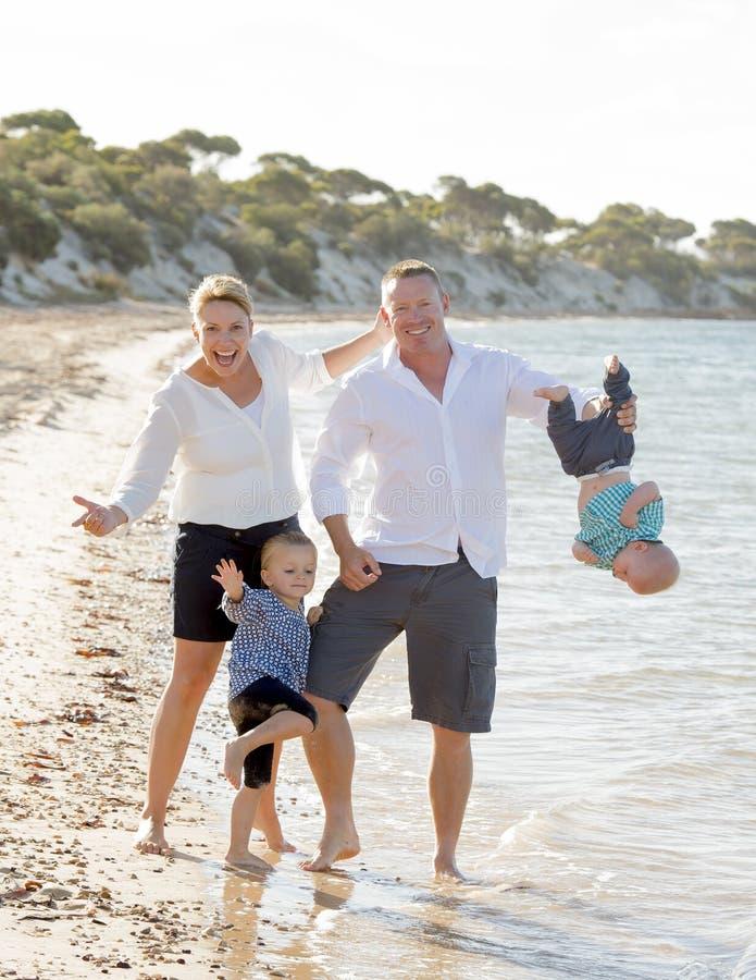 Familia hermosa feliz joven que juega junto en la playa que disfruta de vacaciones de verano fotos de archivo