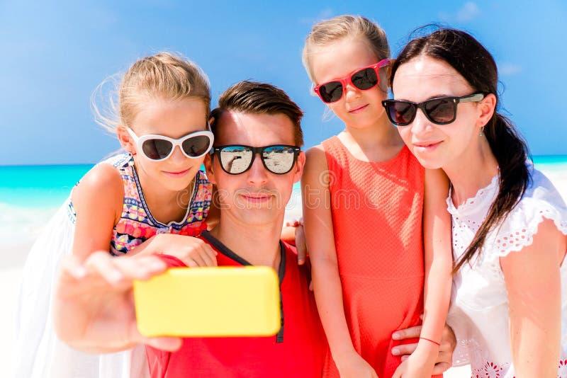 Familia hermosa joven que toma el retrato del selfie en la playa fotos de archivo libres de regalías