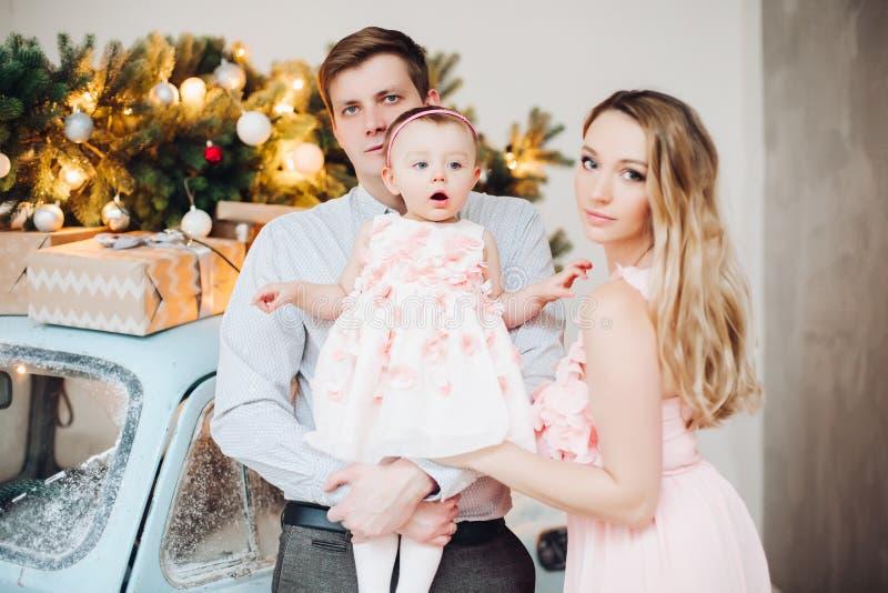 Familia hermosa que presenta junto cerca del coche retro azul de la Navidad fotografía de archivo libre de regalías