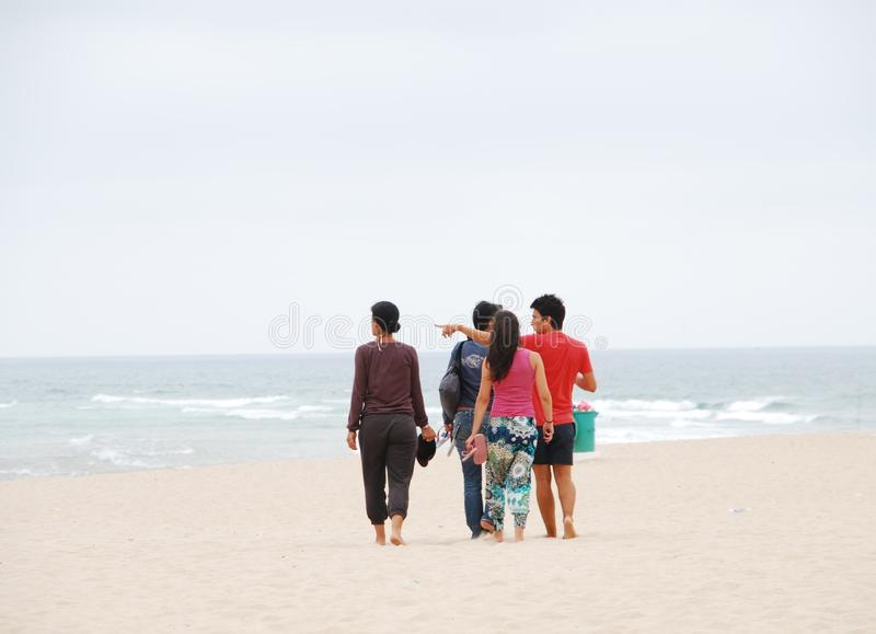 Familia hermosa que recorre en la playa foto de archivo libre de regalías