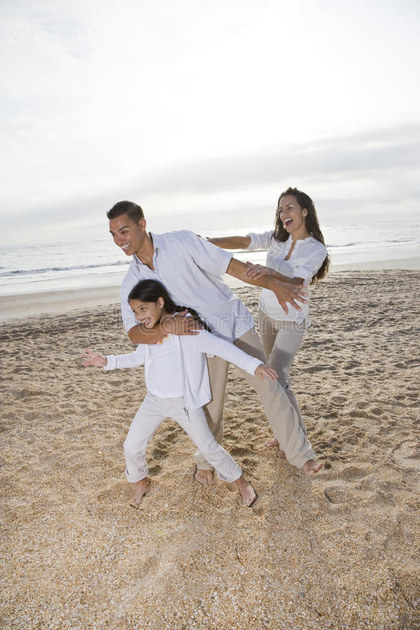 Familia hispánica con la muchacha que se divierte en la playa fotos de archivo