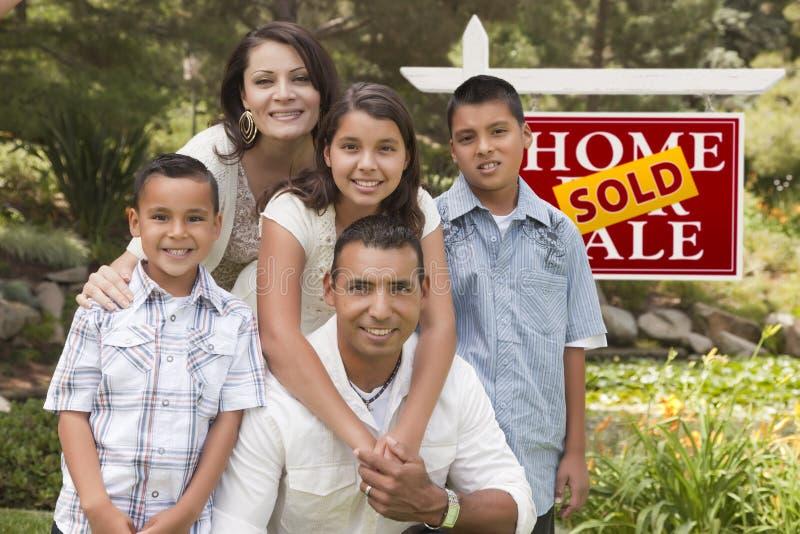 Familia hispánica delante de la muestra vendida de Real Estate foto de archivo