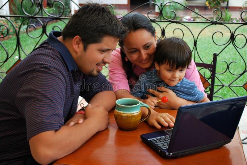 Familia hispánica en la computadora portátil foto de archivo libre de regalías