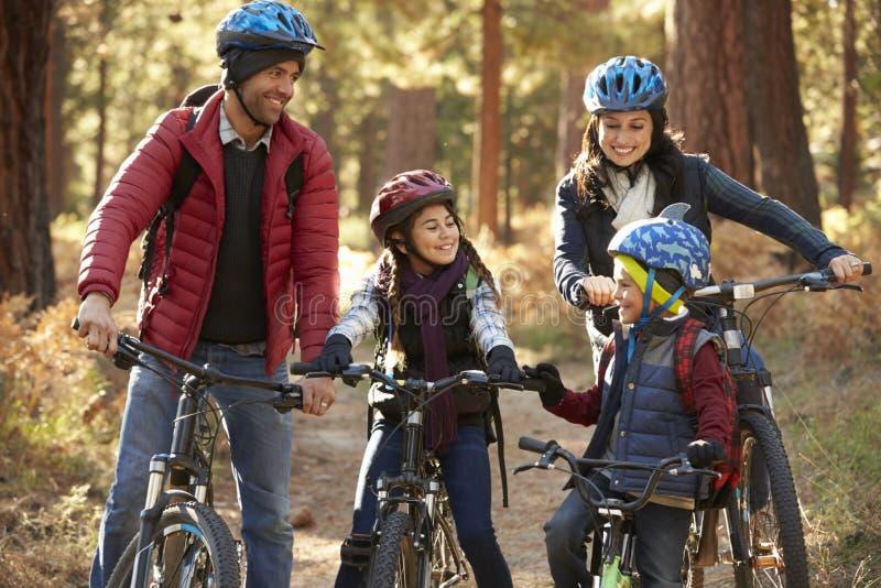 Familia hispánica en las bicis en un bosque que mira uno a imagen de archivo libre de regalías