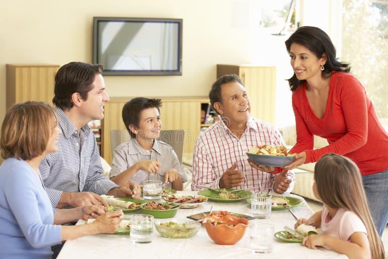 Familia hispánica extendida que disfruta de la comida en casa foto de archivo libre de regalías