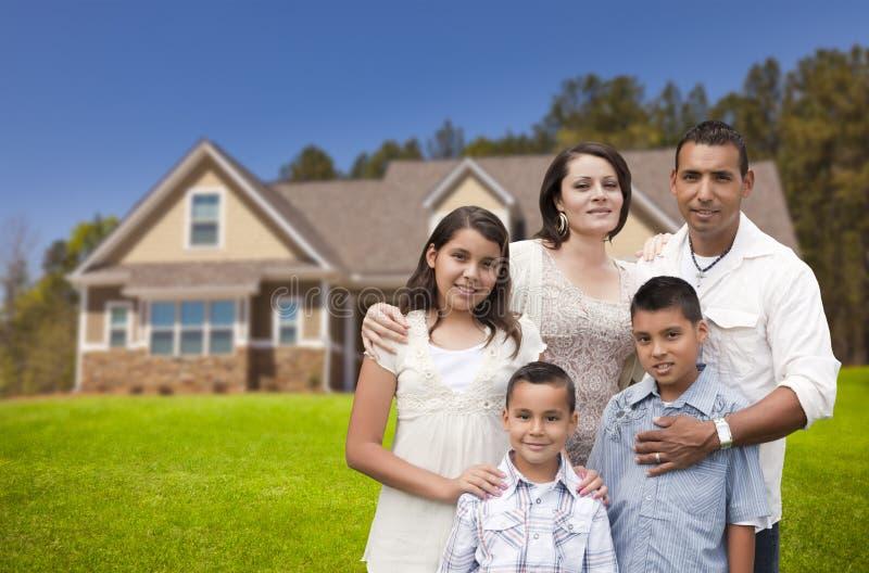 Familia hispánica joven delante de su nuevo hogar fotos de archivo libres de regalías