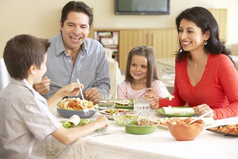 Familia hispánica joven que disfruta de la comida en casa imagenes de archivo