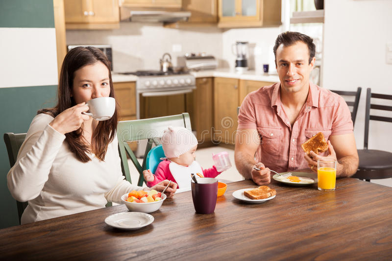 Familia hispánica que goza del desayuno en casa fotografía de archivo