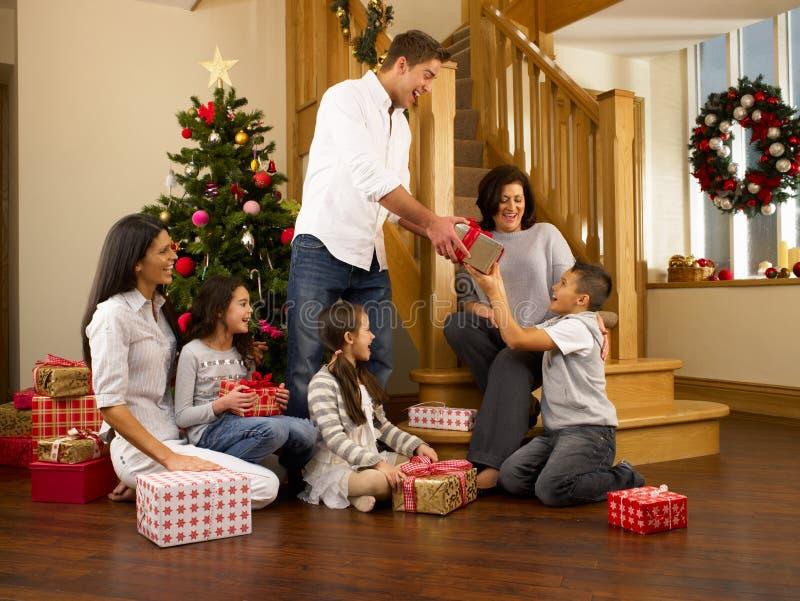 Familia hispánica que intercambia los regalos en la Navidad imagenes de archivo