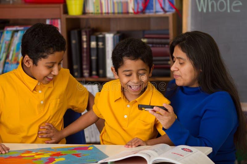 Familia hispánica que mira que se divierte con rompecabezas y el teléfono imagen de archivo libre de regalías