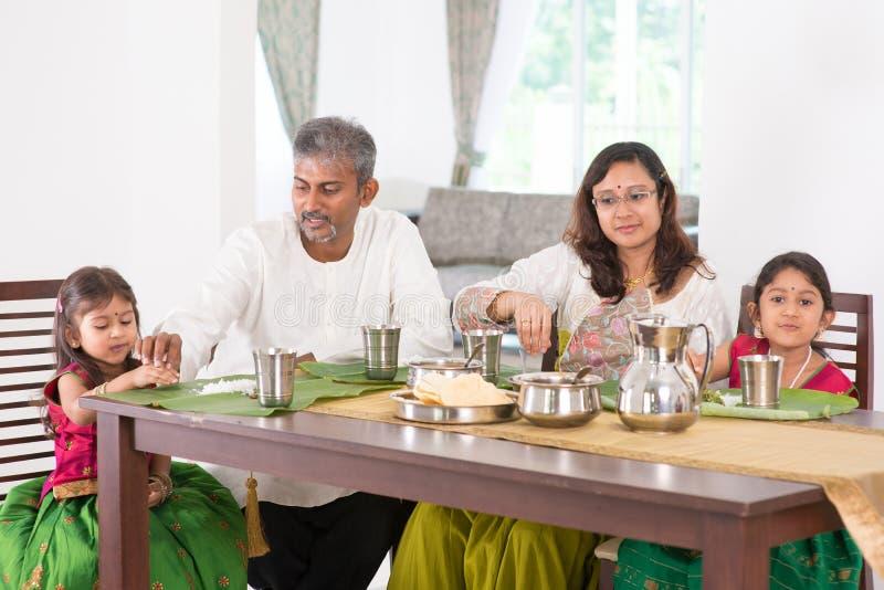 Familia india que cena en cocina imagenes de archivo