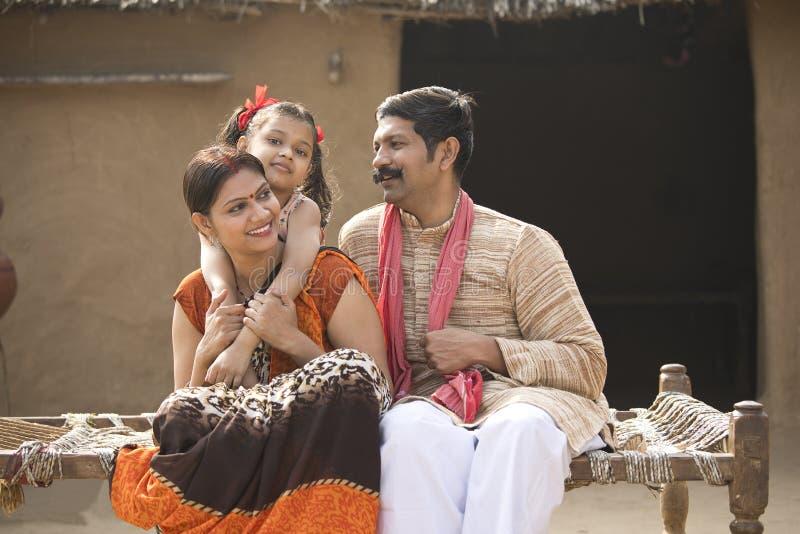 Familia india que se sienta en cama tradicional en pueblo fotos de archivo libres de regalías