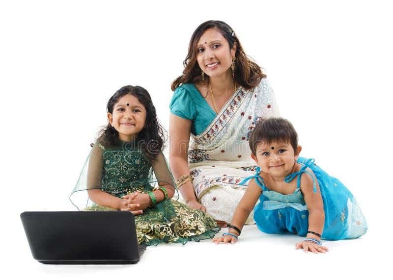 Familia india tradicional con la computadora portátil fotografía de archivo libre de regalías